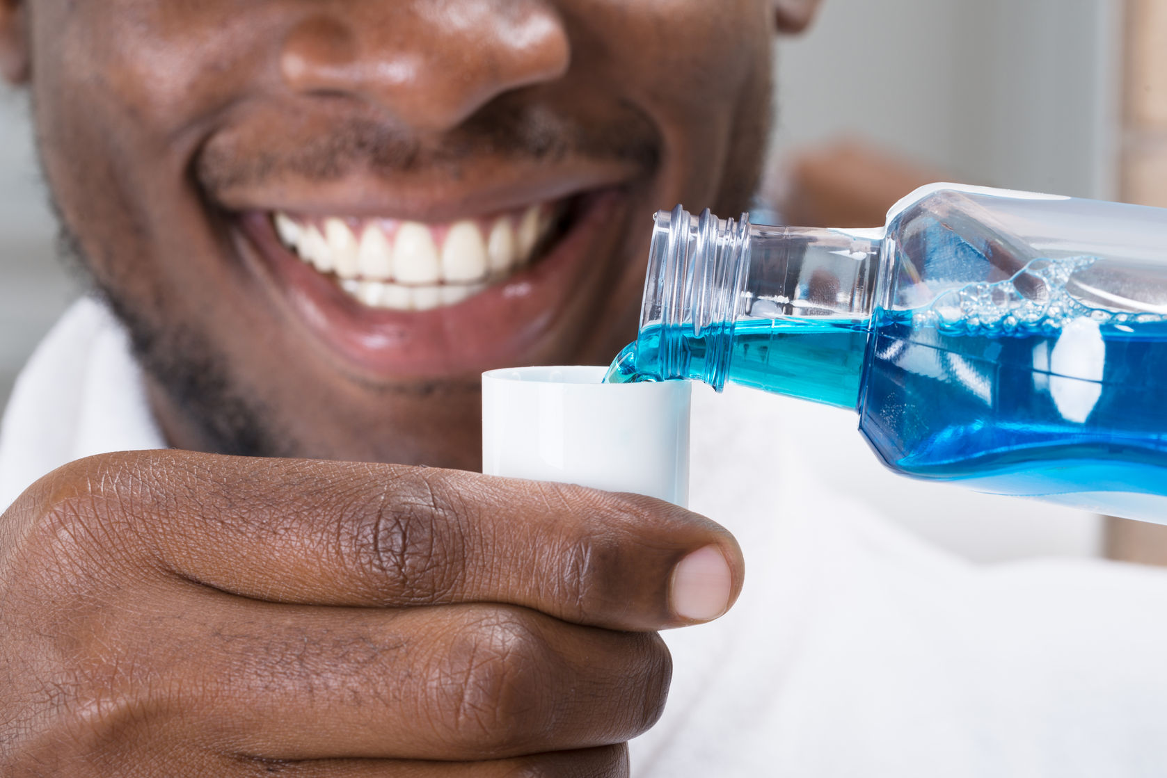 61134869 - close-up of a smiling african man pouring mouthwash into cap